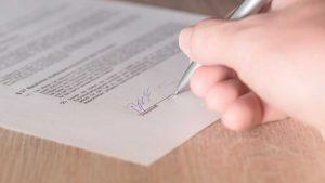 Imagem de mão assinando um contrato usando caneta prateada